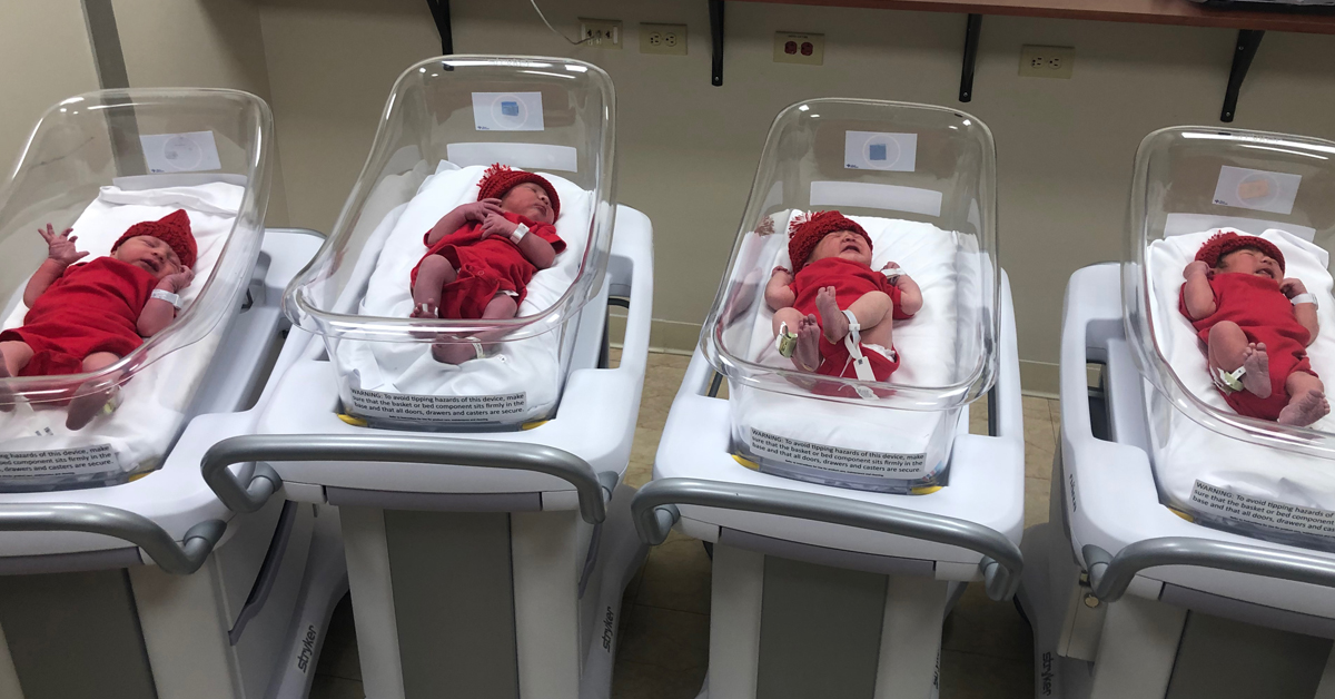 Newborn babies in hospital wear red onesies and hats for american heart month
