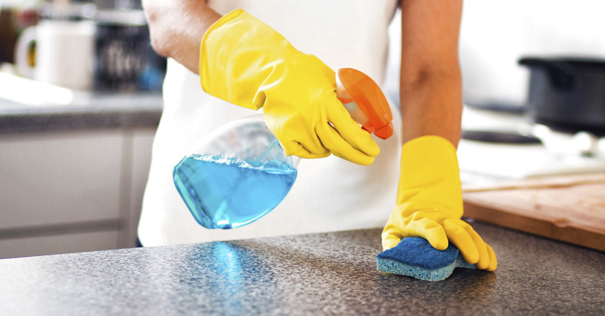 Person disinfecting kitchen counter top with cleaning solution