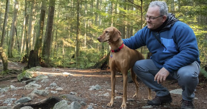 Man practicing social distancing with his dog in the woods
