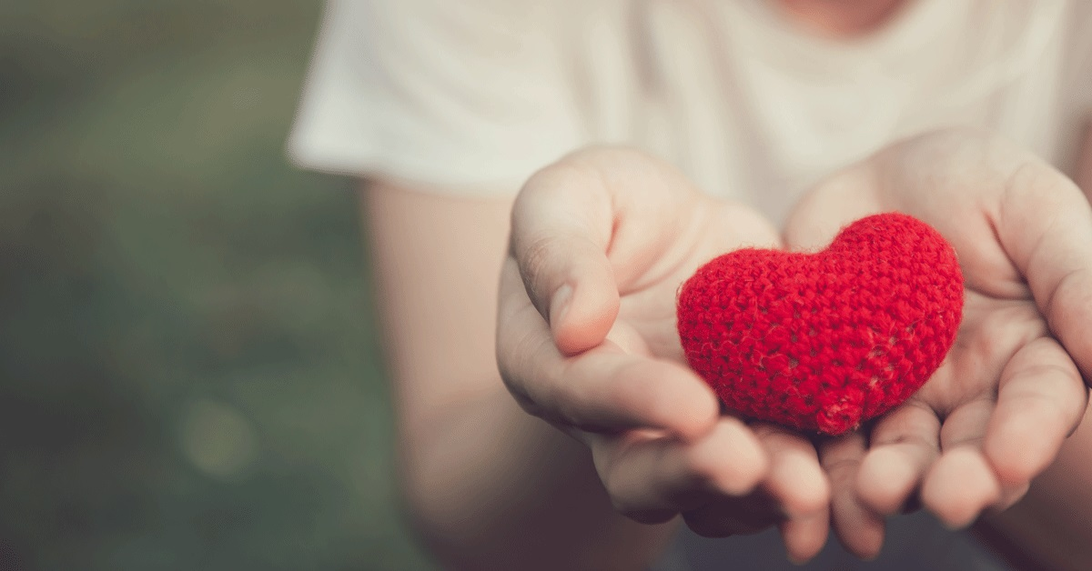 An individual holding a toy heart in their hands during a reflection.