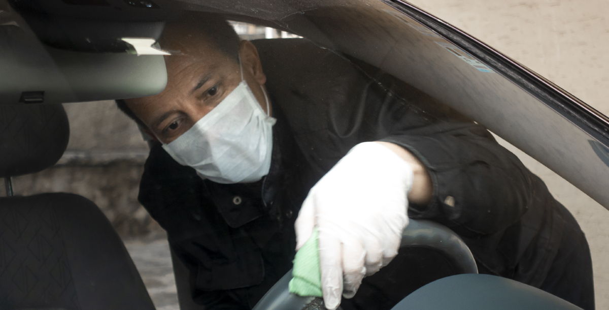 A man disinfecting his car while wearing a face covering.