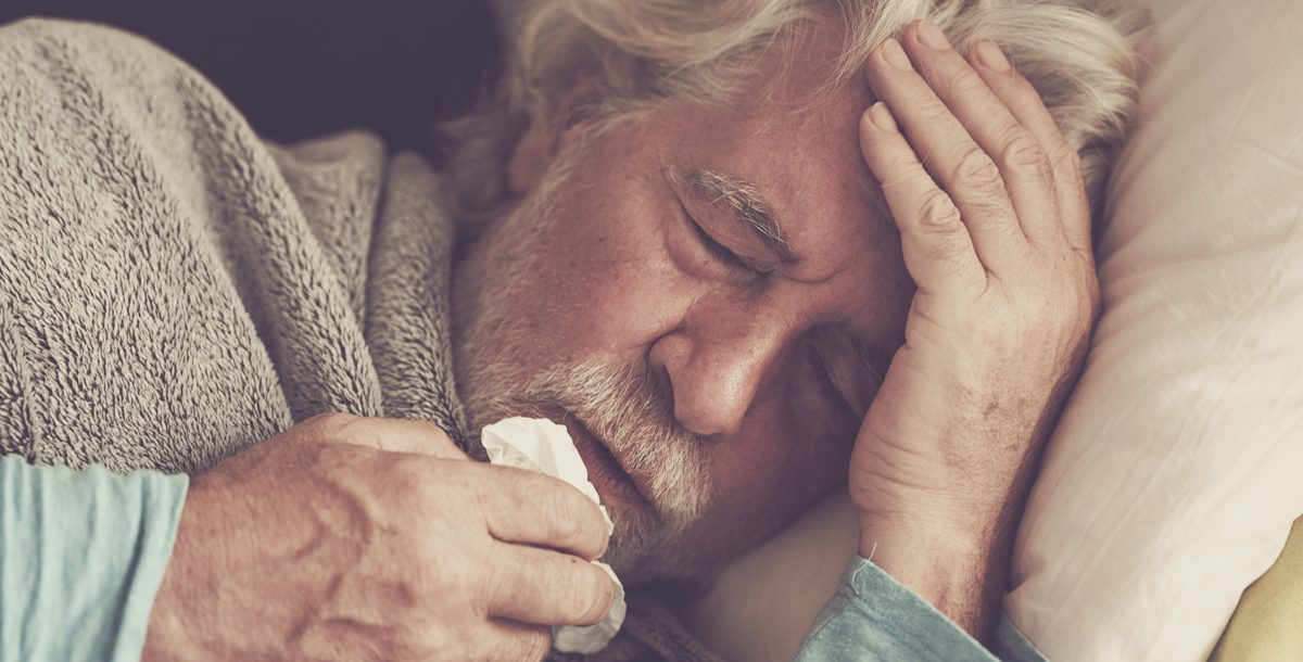 Sick man managing his illness symptoms at home