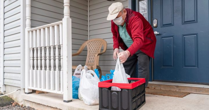 Older individuals taking grocery delivery into the house during COVID-19.