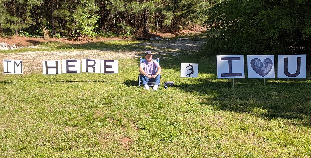 Dennis sitting outside Bon Secours St. Francis Cancer Center with his signs for Diana.