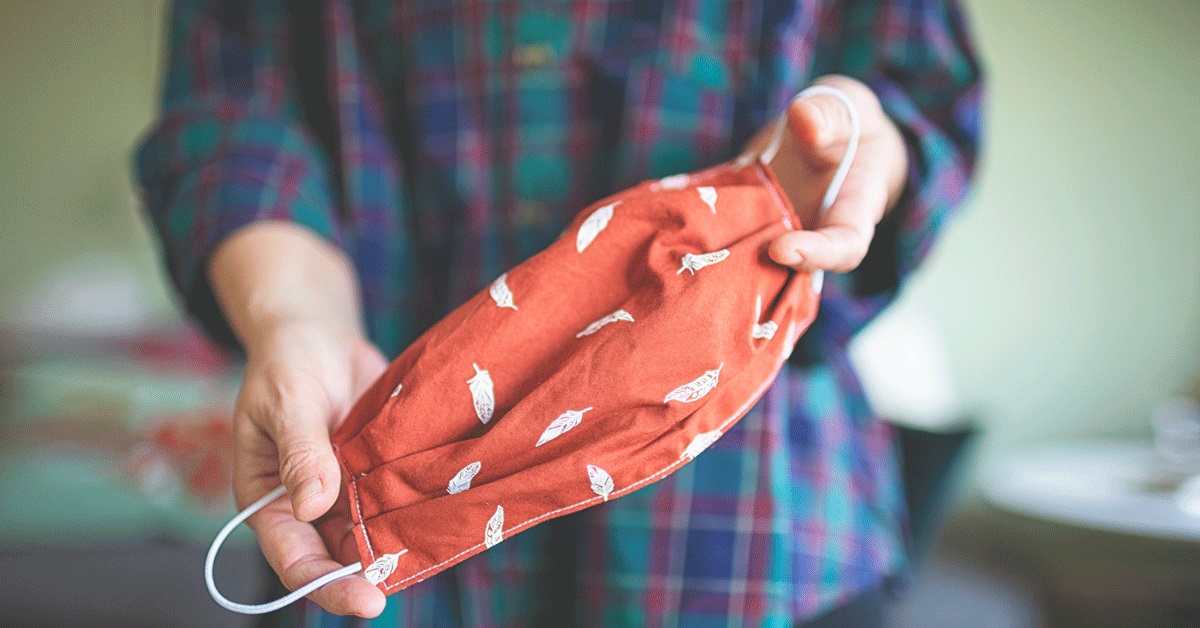A person holding a homemade cloth face covering