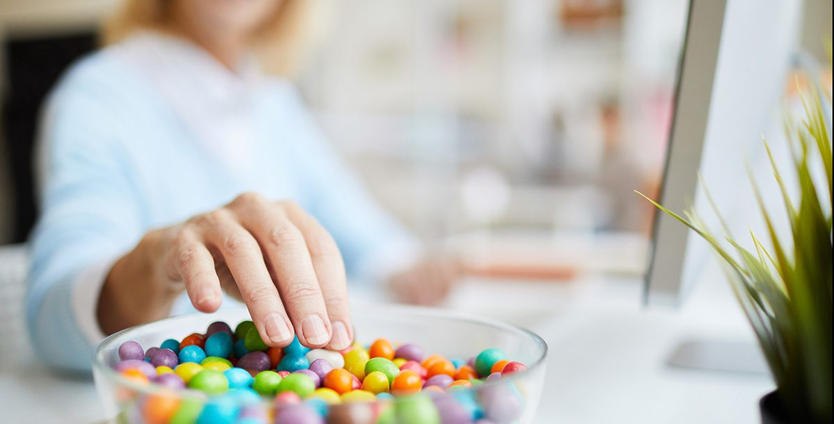 A woman stress snacking candy at home during COVID-19