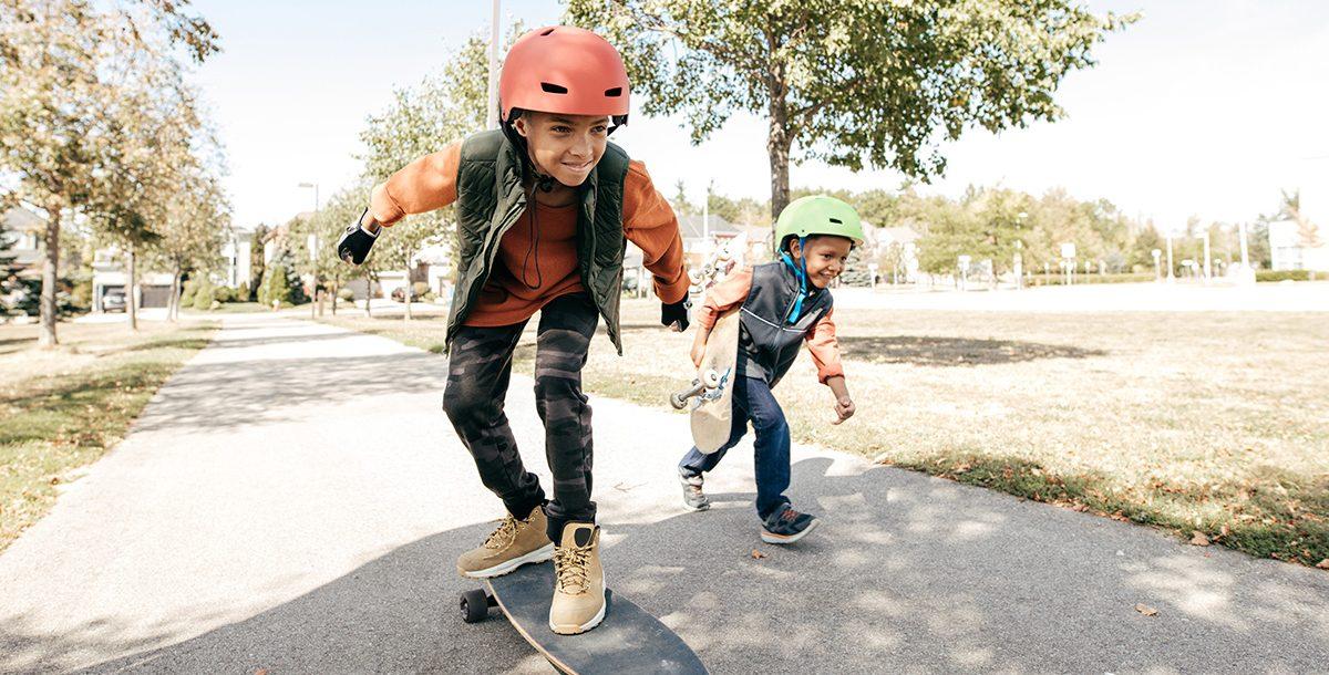 Two kids wearing helmets while skateboarding outside.
