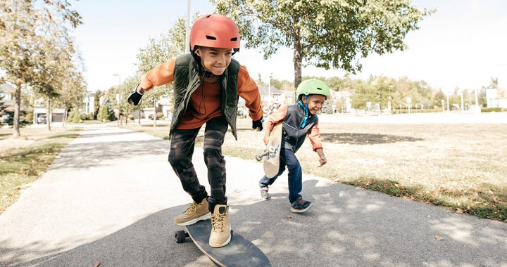 Two kids wearing helmets while skateboarding outside.