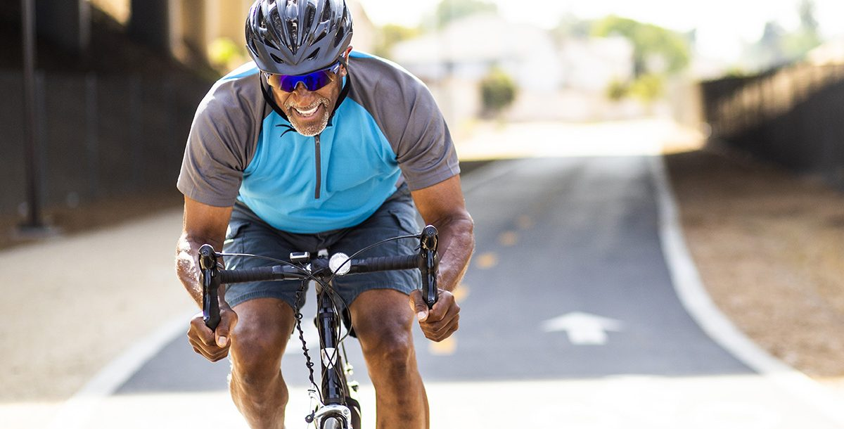 A man working out by cycling outside during the summer months