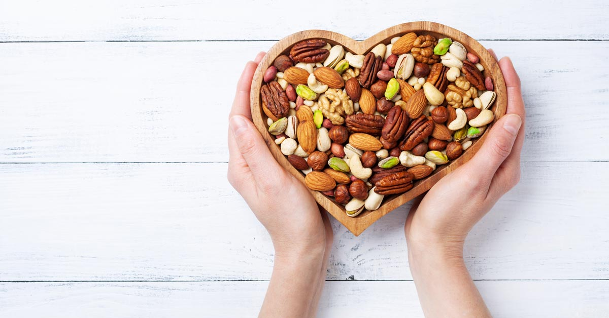 A photo of heart healthy nuts in a heart-shaped bowl.