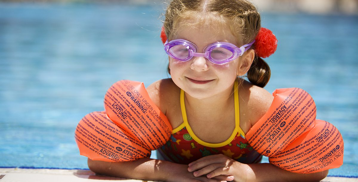 A little girl swimming in a pool with water wings.
