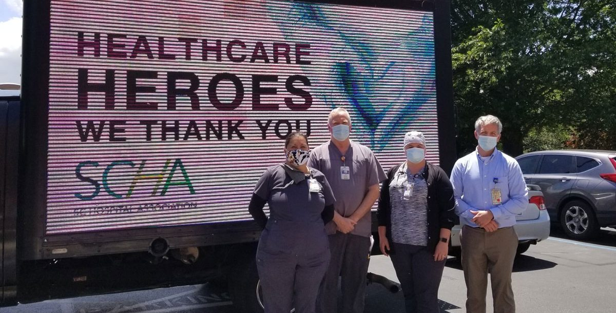 A group of Bon Secours respiratory therapists outside by a health care heroes sign