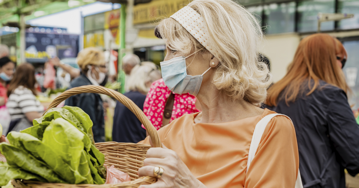 A woman wearing a face mask to a farmers market during COVID-19.