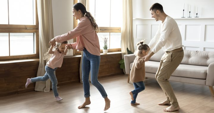 Parents and kids having a dance party together in their living room.