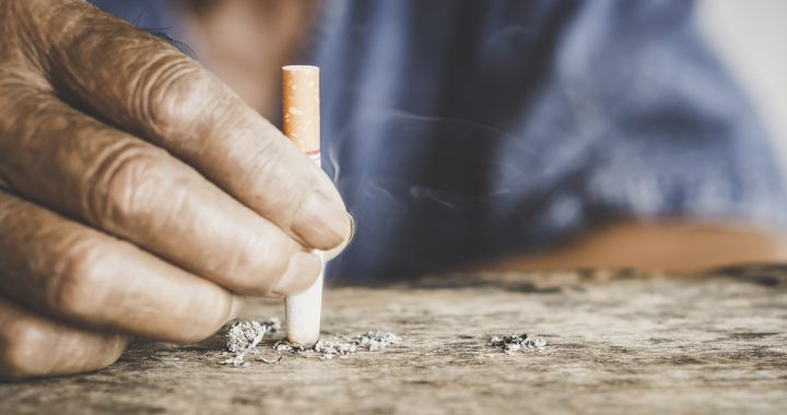 A person putting out a cigarette.