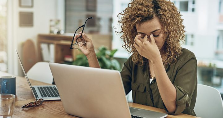 A woman experiencing digital eye strain while working from home.