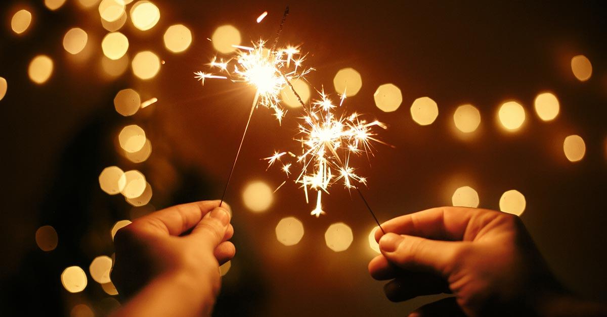 Two people holding sparkler fireworks.