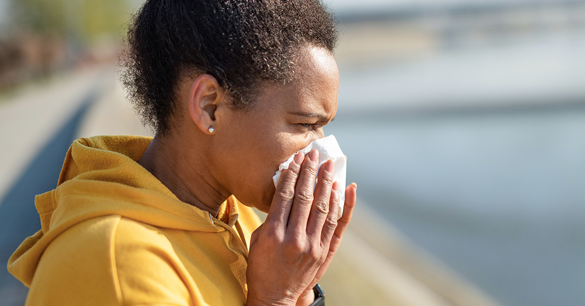 A woman sneezing into a tissue during COVID-19