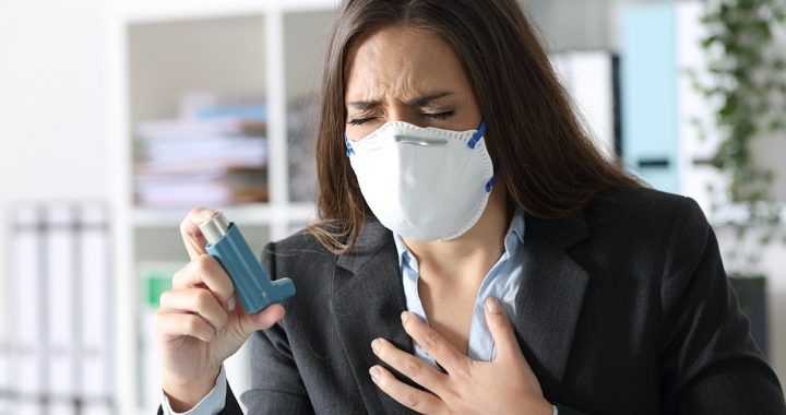 A woman suffering from asthma and using an inhaler.