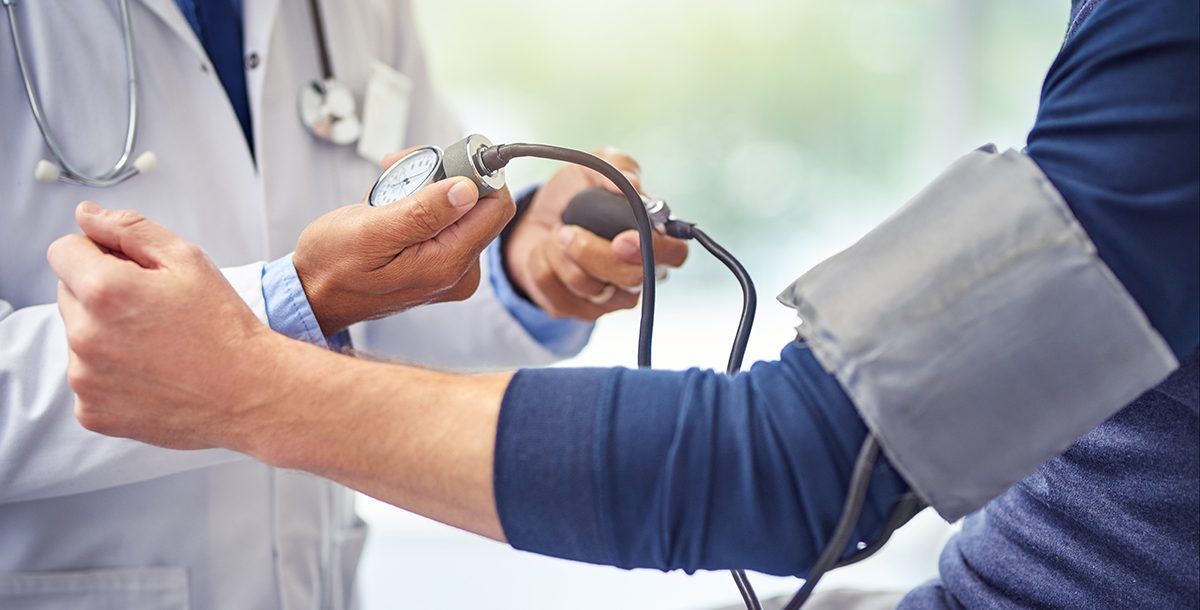 A person checking their blood pressure with their health care provider.