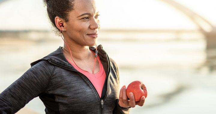A woman eating an apple after exercising to help lower her cholesterol.
