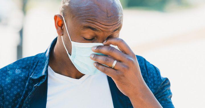 A man experiencing a headache while wearing a face mask.