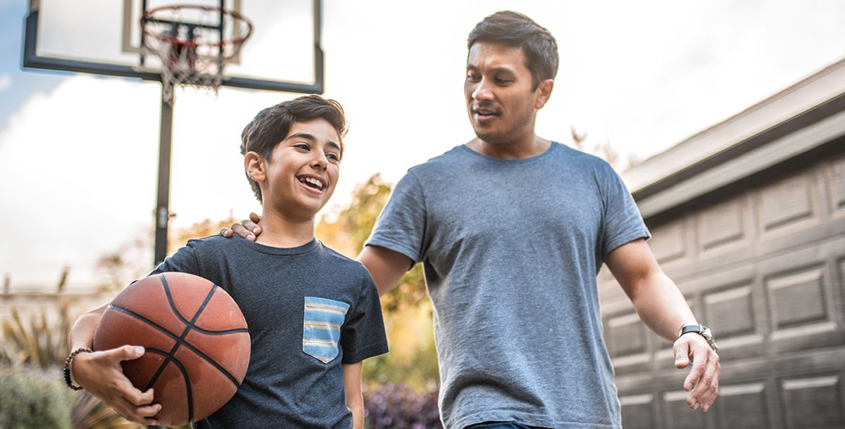 A father playing basketball with his son outside during COVID-19.