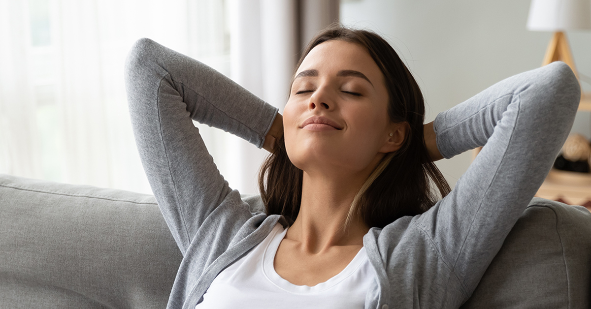 A woman taking a moment to practice a breathing exercise while experiencing anxiety.