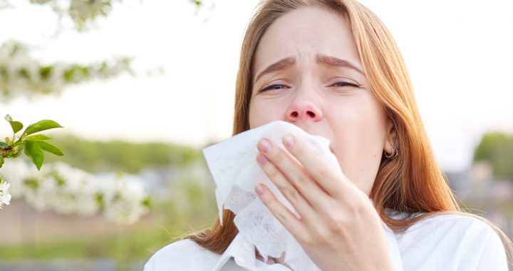 A woman using a tissue to cover her sneeze.