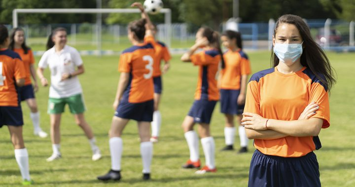 A girl at soccer practice wearing a face mask on the sidelines.
