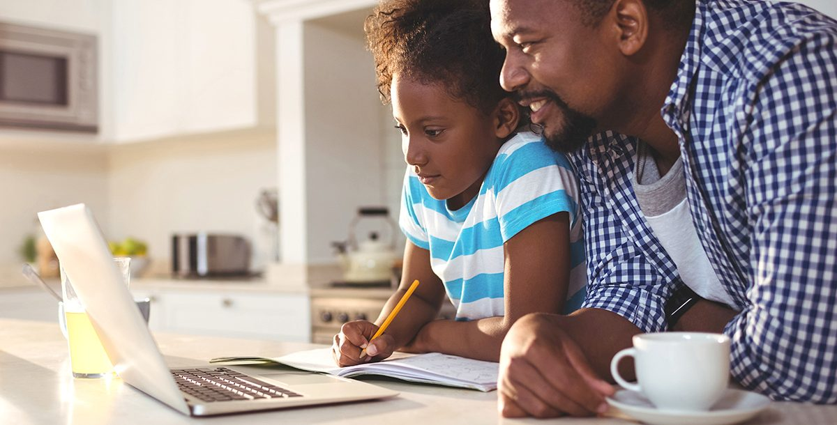 A father helping is daughter with e-learning at home during COVID-19.
