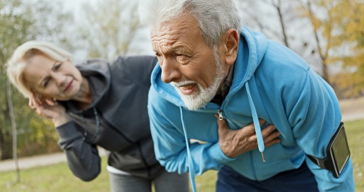 A man experiencing one of the early signs of a heart attack: chest pain.