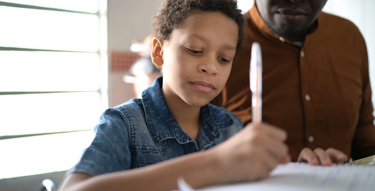 A young boy working on school work at home with a parent.