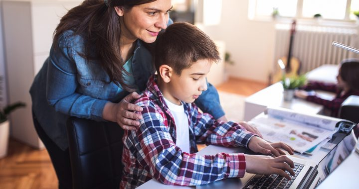 A mother helping her son with virtual learning at home during the back-to-school season.