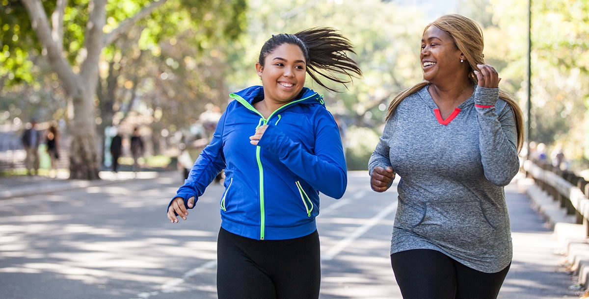 Two women exercising outside.