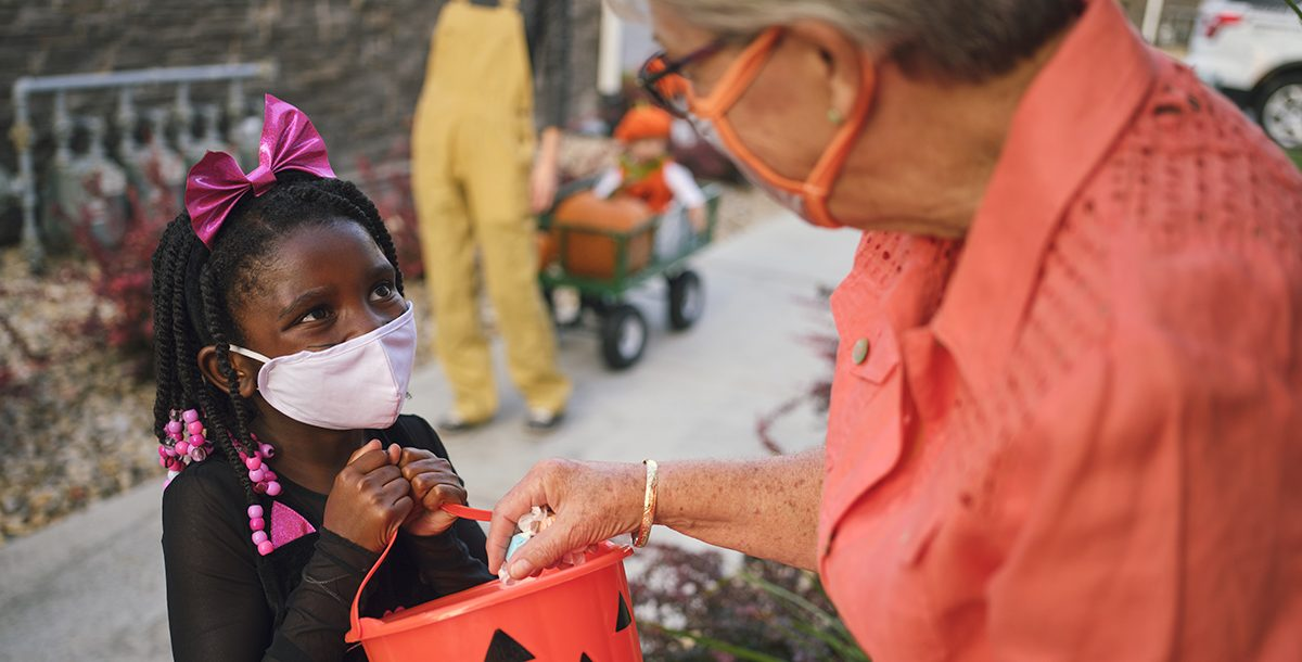 A child trick or treating with a face mask on during Halloween.