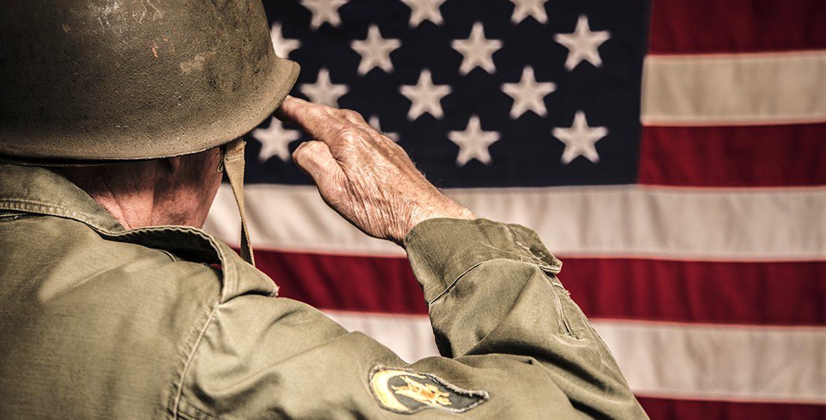 A veteran saluting the American flag.