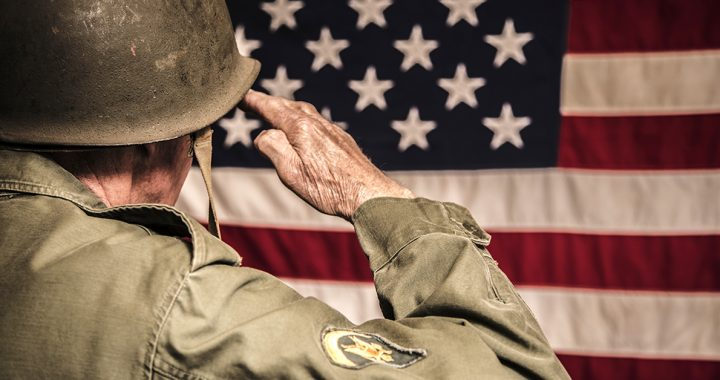 A veteran saluting the American flag.