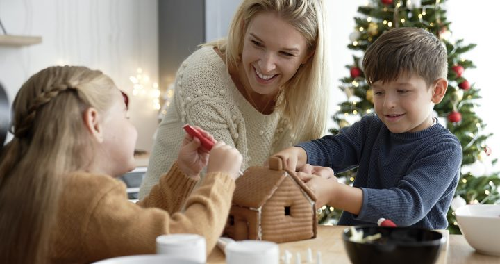 A mom decorating a gingerbread house with her kids.