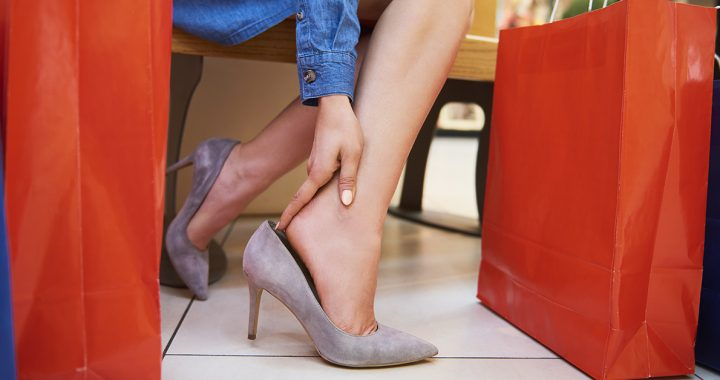 A woman experiencing foot pain while shopping.