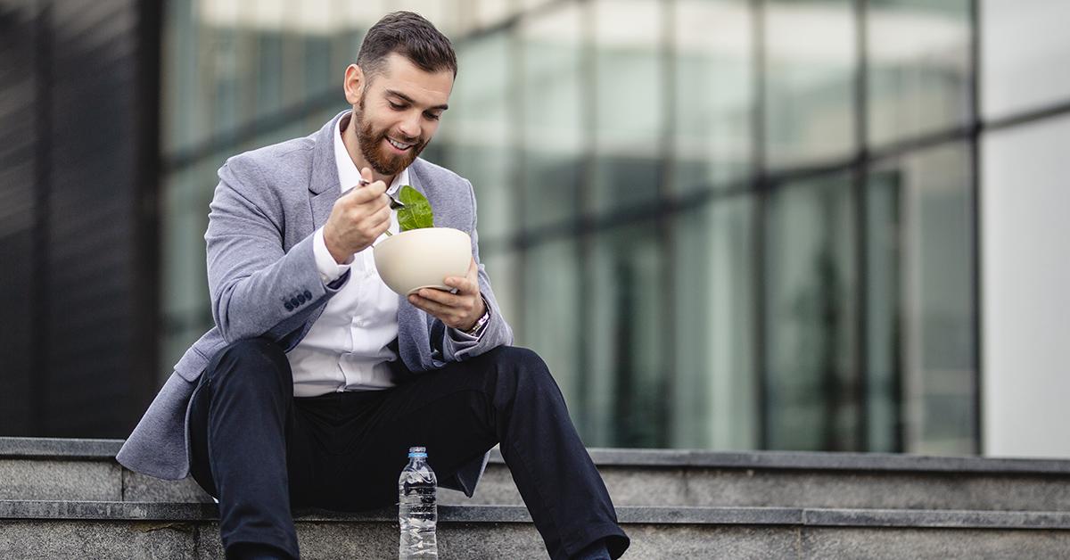 A young man taking a lunch break outside.