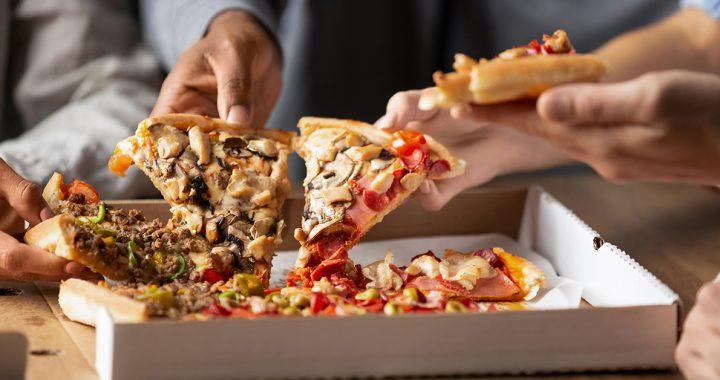 A family enjoying pizza takeout.