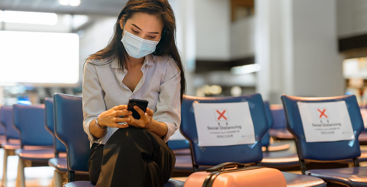 A woman practicing social distancing and wearing a face mask at the airport.