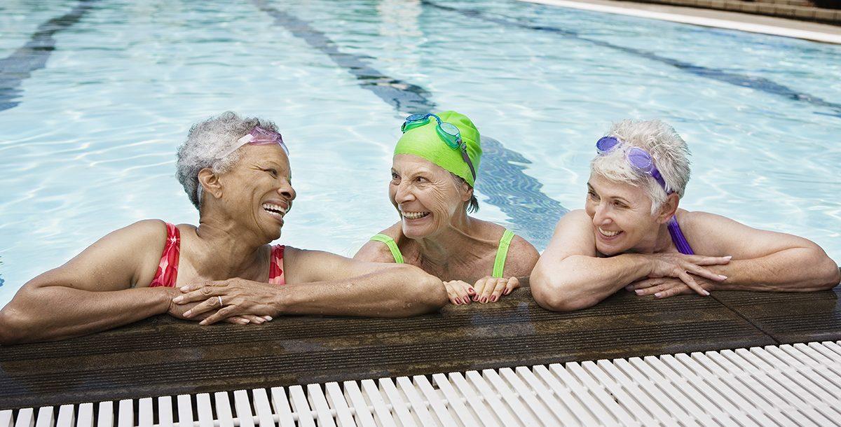 Three senior friends swimming together.