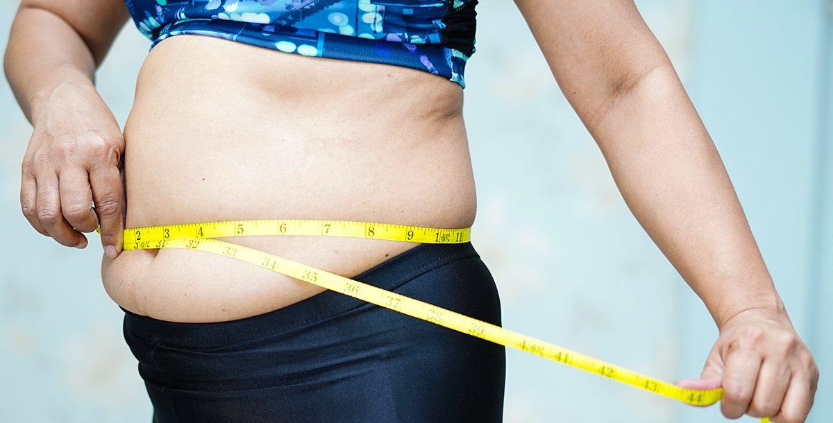 A person measuring their waist.