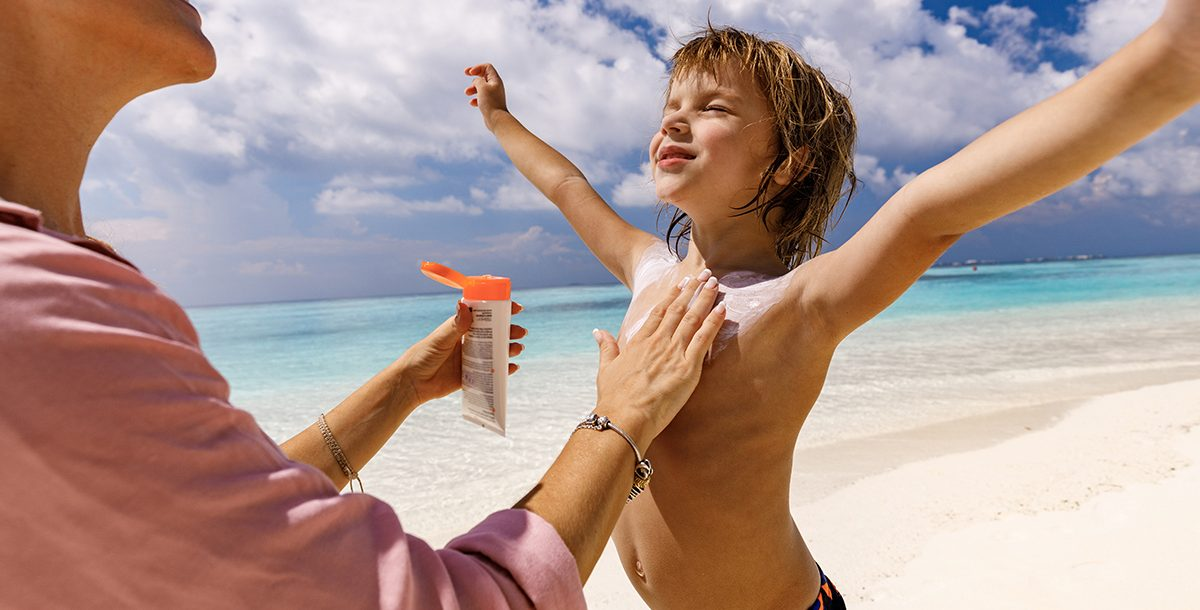 A parent applying sunscreen to their child.