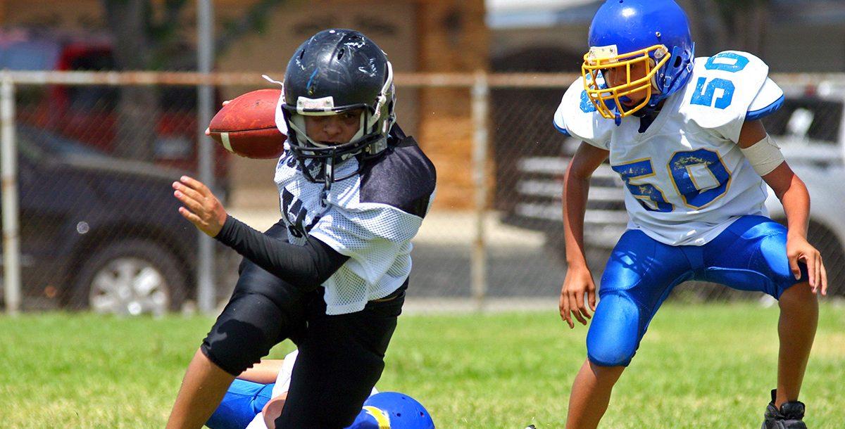 Two kids playing football.