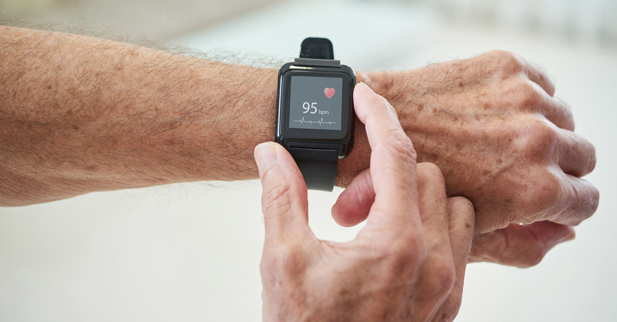 A person checking their heart rate using a smart watch.