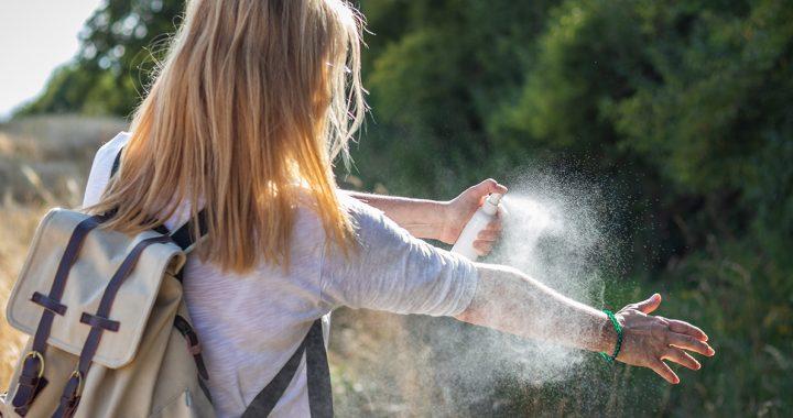 A woman putting on bug spray.